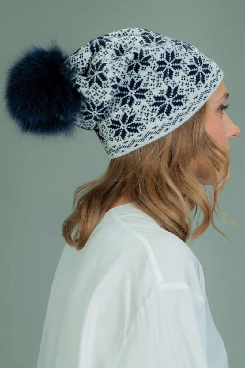 slouchy wool hat with fur pom-pom with dark blue star pattern in white background