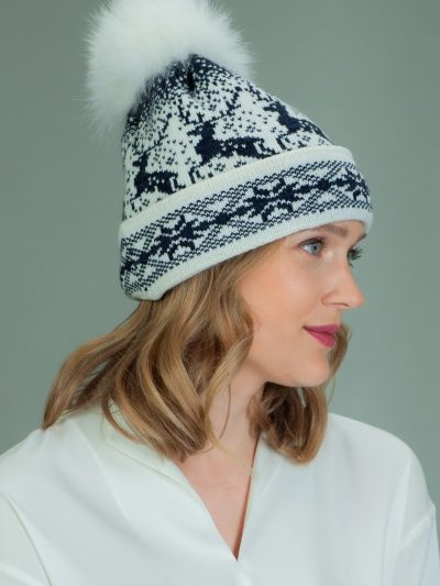 wool hat with fur pom-pom in dark blue Santa deer pattern in white background