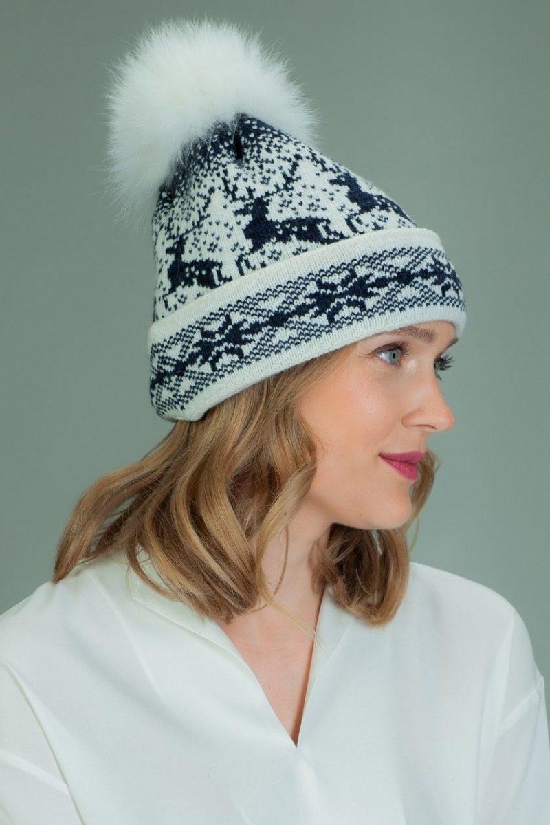 wool hat with fur pom-pom in dark blue Santa deer pattern in white background