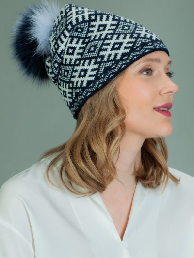wool hat with fur pom pom in white rhombus pattern in dark blue background