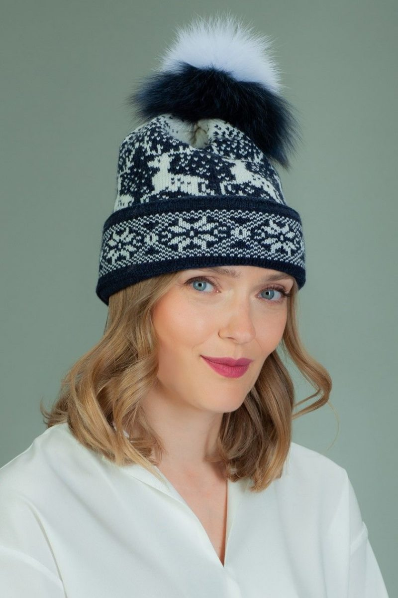 knit wool hat with fur pom pom in white santa deer pattern in dark blue background