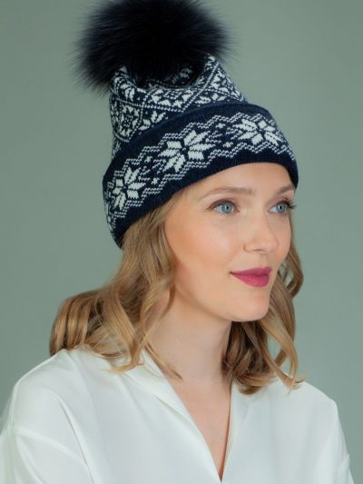 wool hat with fur pom-pom in white star pattern in dark blue background